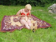 Naughty older woman stripping and spreading her legs outdoors to masturbate with a dildo
